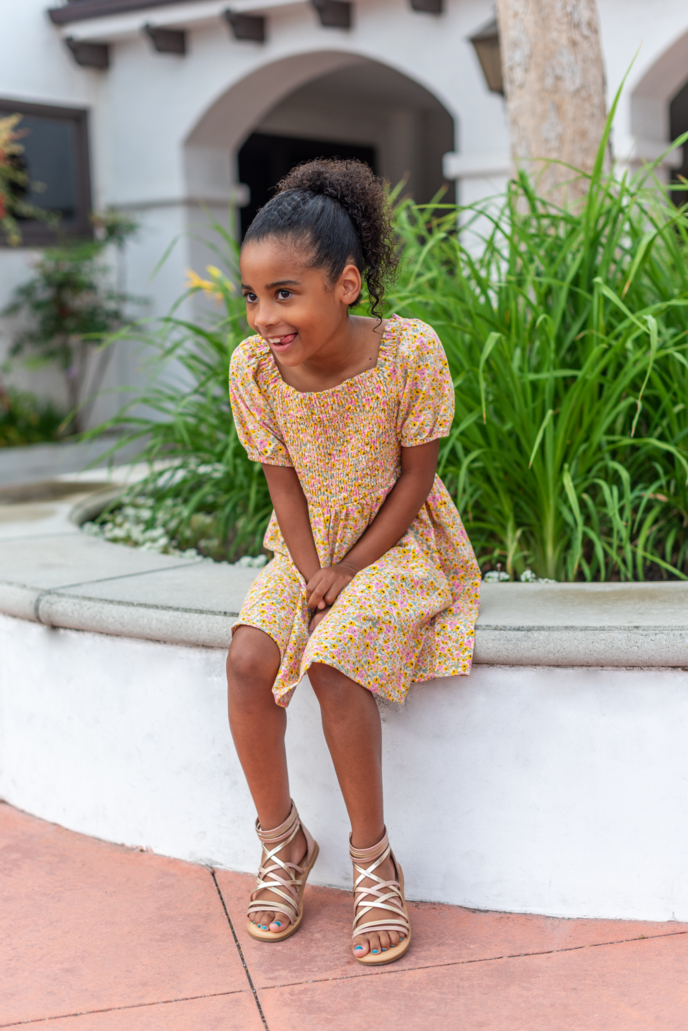 Mommy and Me Outfits by popular LA fashion blog, Posh in Progress: image of a young girl sitting outside and wearing a floral print dress and gold strap gladiator sandals.