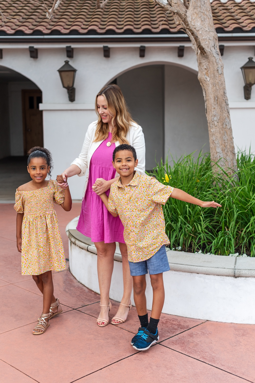 Mommy and Me Outfits by popular LA fashion blog, Posh in Progress: image of a mom and her two kids standing outside and wearing a white blazer, pink dress, nude heel sandals, floral print dress, floral print button up shirt, chambray shorts, gold strap sandals, and blue sneakers.