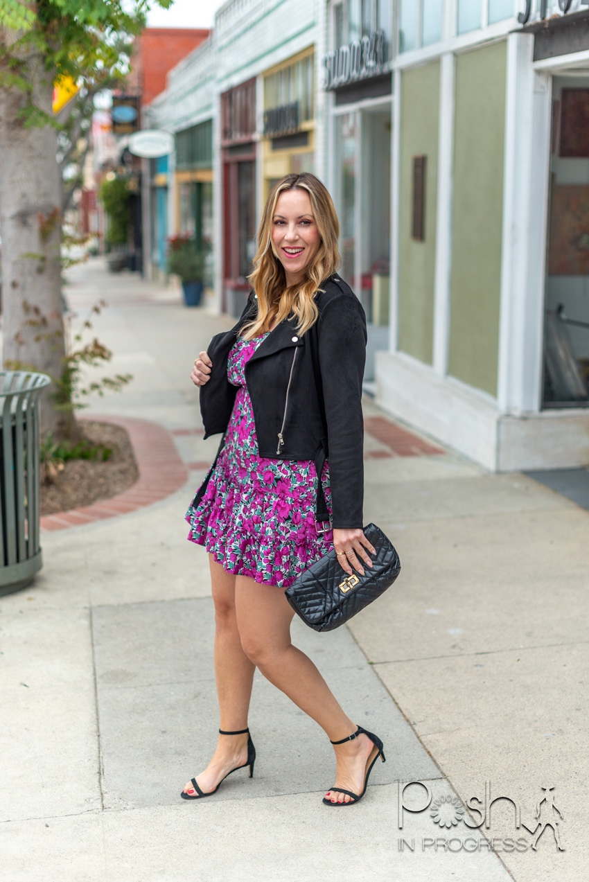 Shein Floral Dresses by popular LA fashion blog, Posh in Progress: image of of a woman standing outside on a sidewalk in front of some shops and wearing a purple floral print ruffle hem Shein dress, leather jacket, black ankle strap sandals, and holding a black clutch.