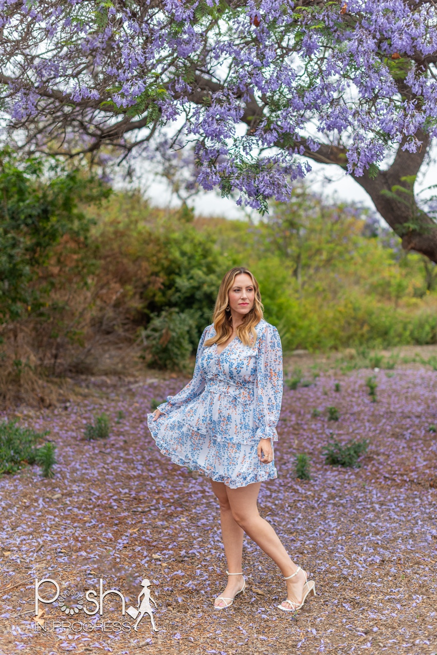 Backless Dresses by popular LA fashion blog, Posh in Progress: image of a woman standing under a jacaranda tree and wearing a white floral print dress with white heel sandals.