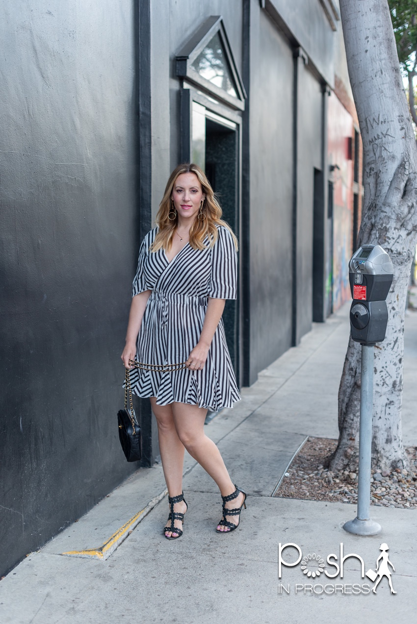Black and White Dresses by popular LA fashion blog, Posh in Progress: image of a woman standing in front of a black building and wearing a black and white stripe dress with black heel sandals.