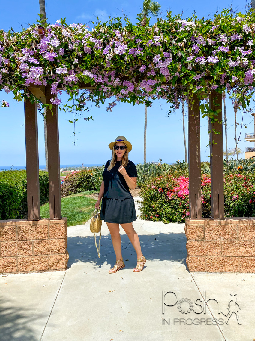 carlsbad flower fields 2 | Carlsbad Flower Fields by popular LA lifestyle blog, Posh in Progress: image of a woman wearing a blue dress, straw sun hat, gold strap sandals, and holding a circle handbag while standing under a pergola with purple flowers growing on top of it.