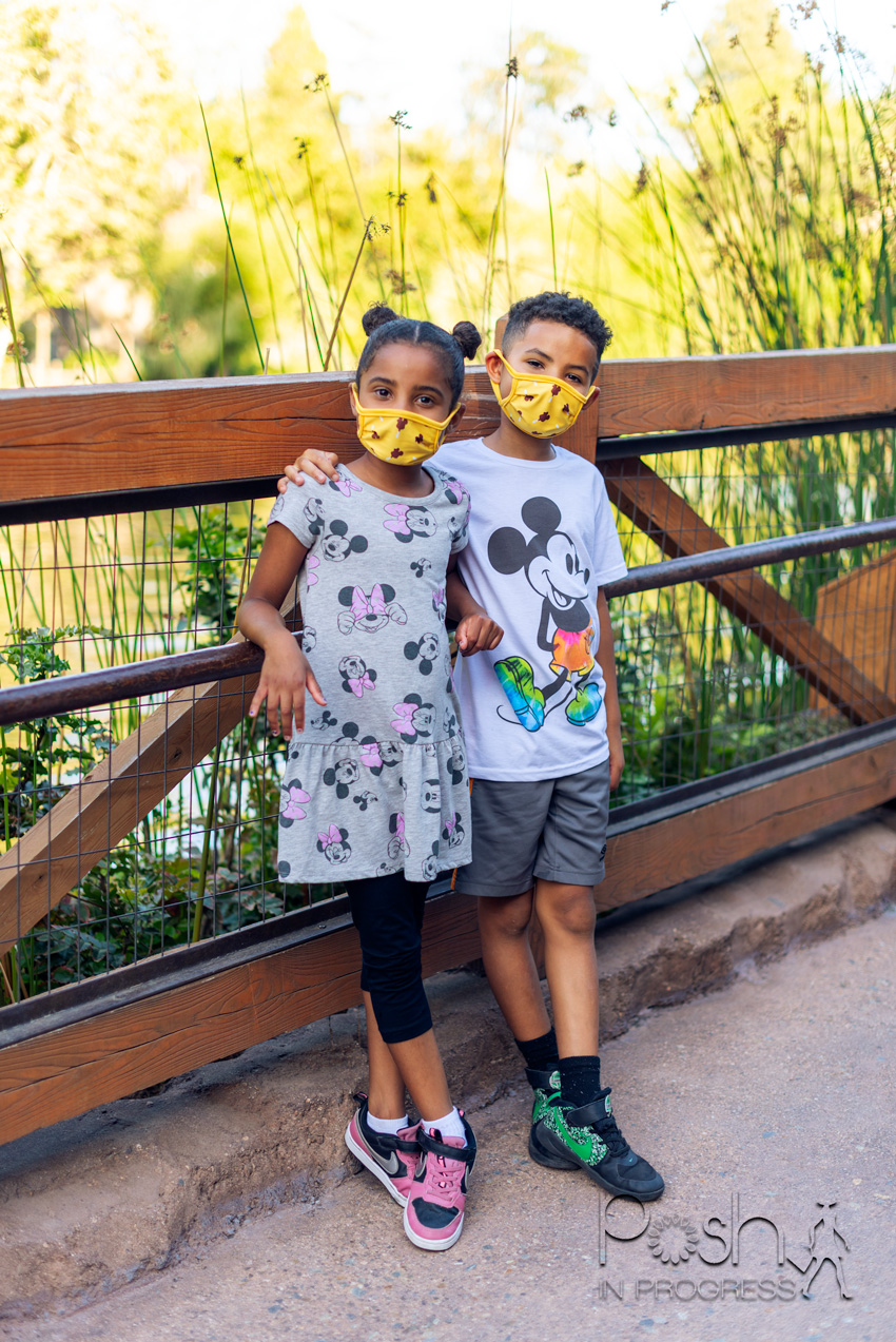 Disneyland Reopening by popular LA lifestyle blog, Posh in Progress: image of a boy and girl standing together on a bridge and wearing Mickey and Minnie Mouse shirts.