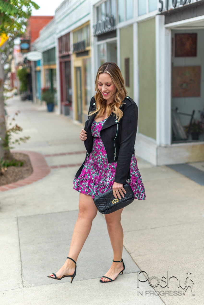 shein floral dress 2 | Shein Floral Dresses by popular LA fashion blog, Posh in Progress: image of of a woman standing outside on a sidewalk in front of some shops and wearing a purple floral print ruffle hem Shein dress, leather jacket, black ankle strap sandals, and holding a black clutch.