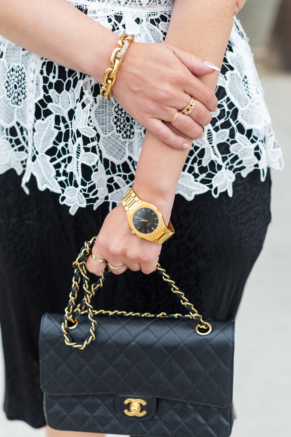 What to Wear by popular LA fashion blog, Posh in Progress: image of a woman wearing a white lace top, black skirt gold watch, gold link bracelet and black quilted Chanel bag.