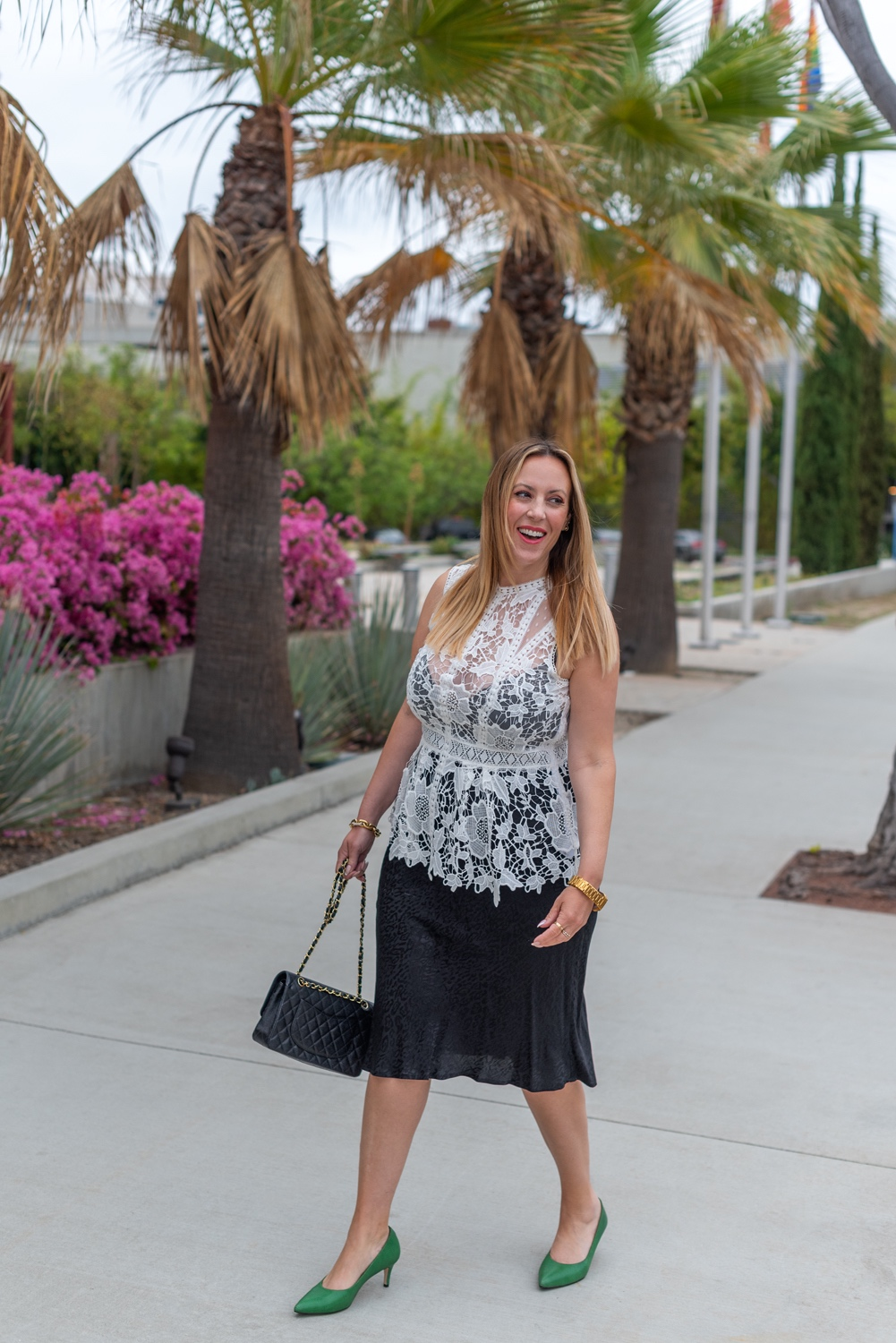 What to Wear by popular LA fashion blog, Posh in Progress: image of a woman wearing a white lace top, black skirt gold watch, gold link bracelet, green heels, and black quilted Chanel bag.