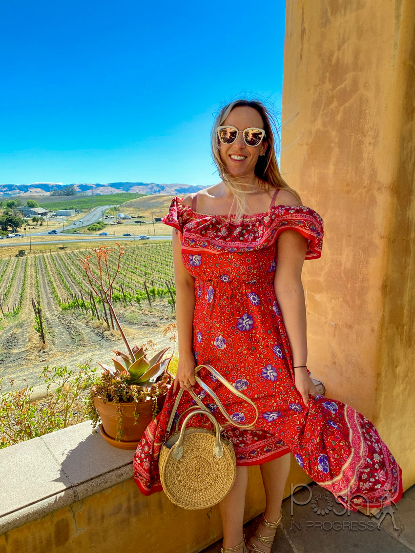 sonoma wine tour 1 | Sonoma Wine Tour by popular LA lifestyle blog, Posh in Progress: image of a woman standing outside at a vineyard and wearing a red and blue floral print off the shoulder maxi dress and holding a woven circular bag.