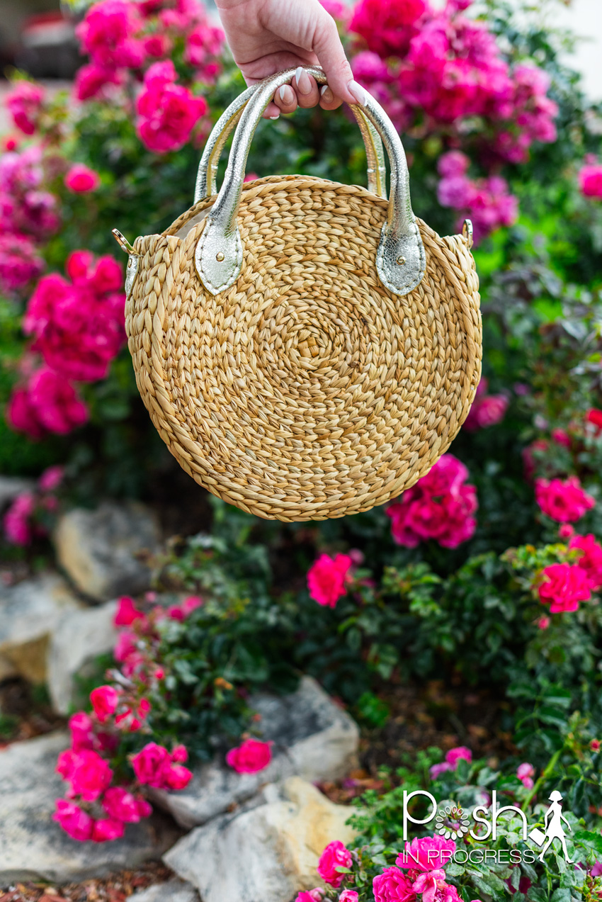 summer straw bags | Summer Straw Bags by popular LA fashion blog, Posh in Progress: image of a woman holding a circular straw bag in front of some pink flowers.
