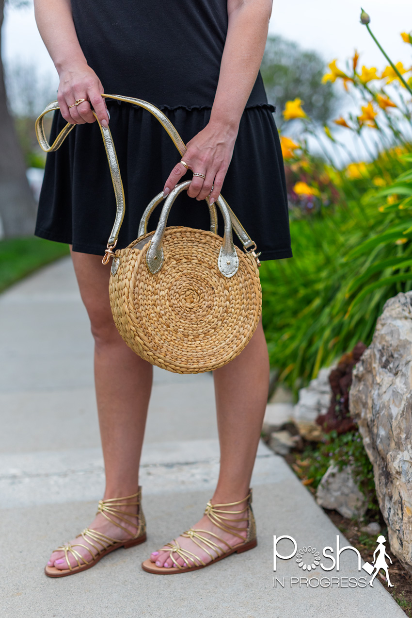 summer straw bags | Summer Straw Bags by popular LA fashion blog, Posh in Progress: image of a woman standing on a sidewalk outside next to some yellow flowers and wearing a black ruffle hem dress and gold strap flat sandals while holding a round circular straw bag.