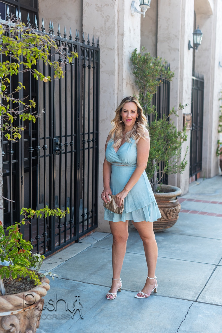 Cami Dress by popular LA fashion blog, Posh in Progress: image of a woman standing outside and wearing a light blue SheIn cami dress with white strap heel sandals while holding a gold clutch.