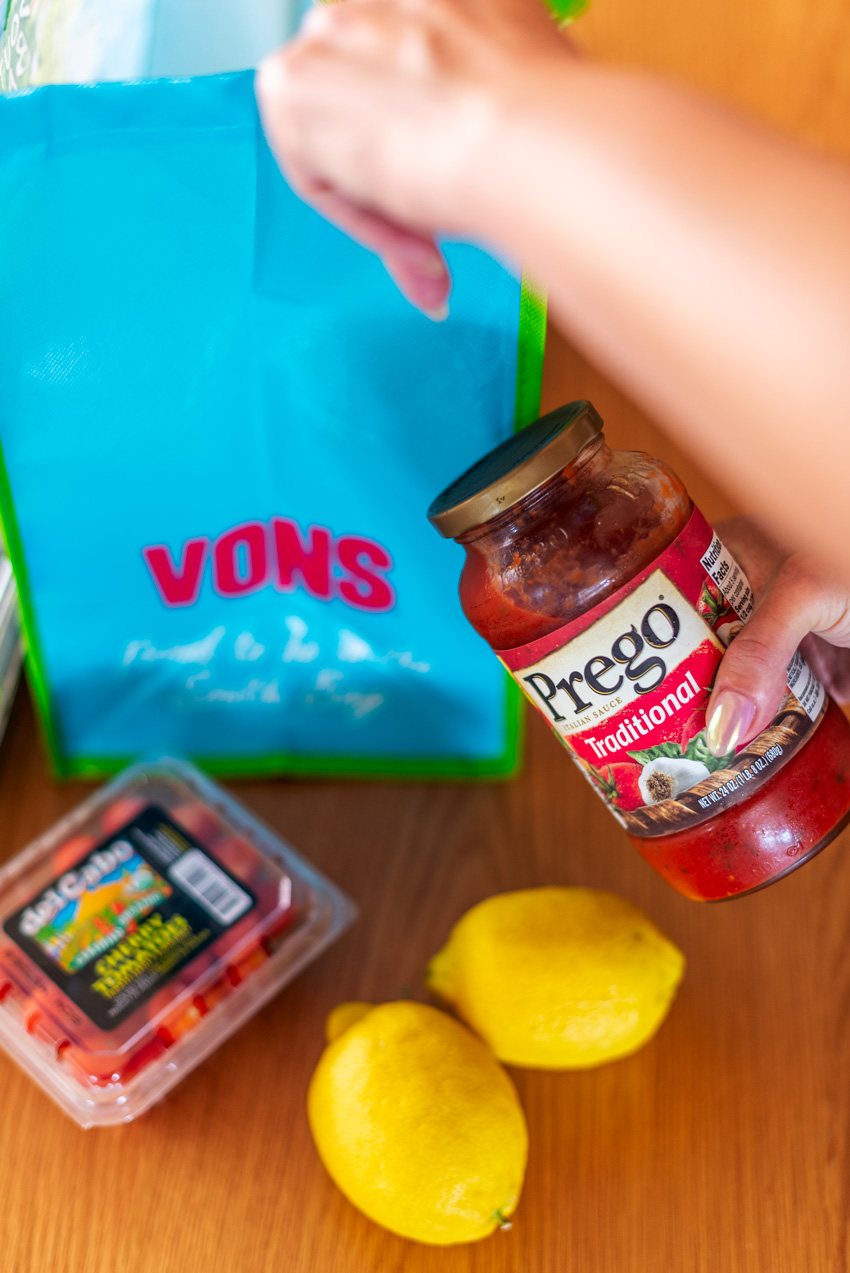 Meatball Sliders by popular LA lifestyle blog, Posh in Progress: image of a woman holding a jar of Prego traditional spaghetti sauce above some lemons and a container of cherry tomatoes next to a Vons shopping bag.