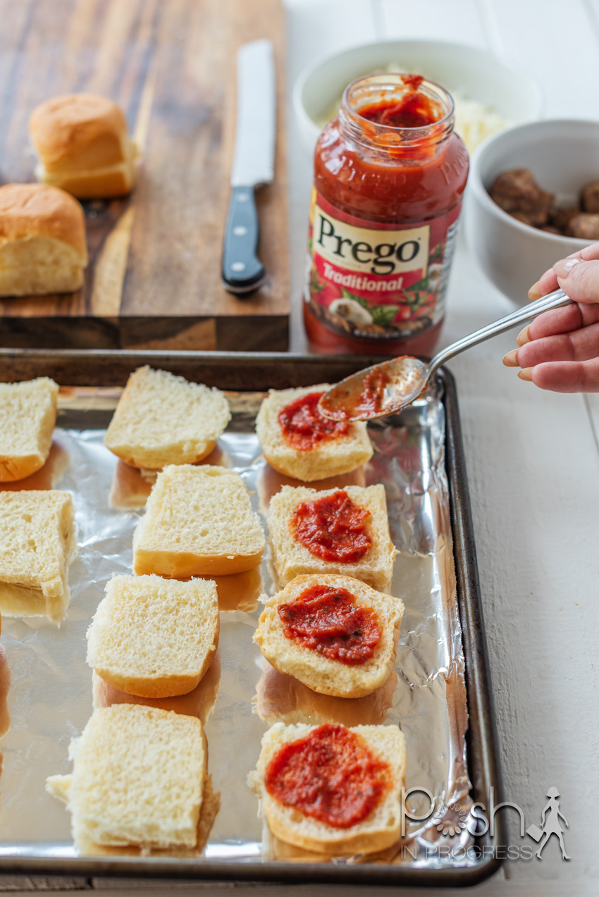 Meatball Sliders by popular LA lifestyle blog, Posh in Progress: image of a woman spreading Prego spaghetti sauce on rolls that have been placed on a baking sheet lined with tin foil.