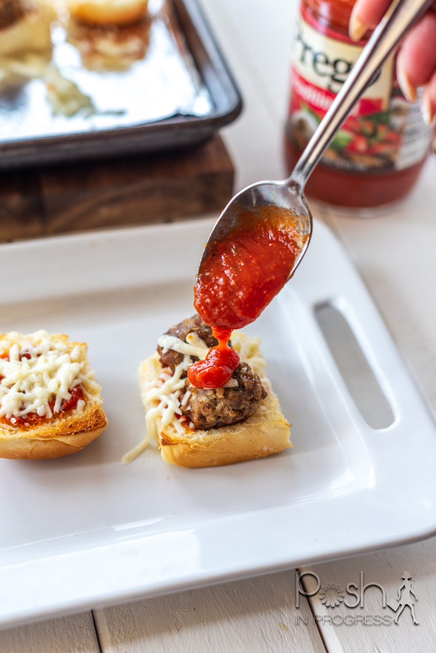 Meatball Sliders by popular LA lifestyle blog, Posh in Progress: image of a woman putting Prego spaghetti sauce on a meatball slider on a white rectangular ceramic tray.