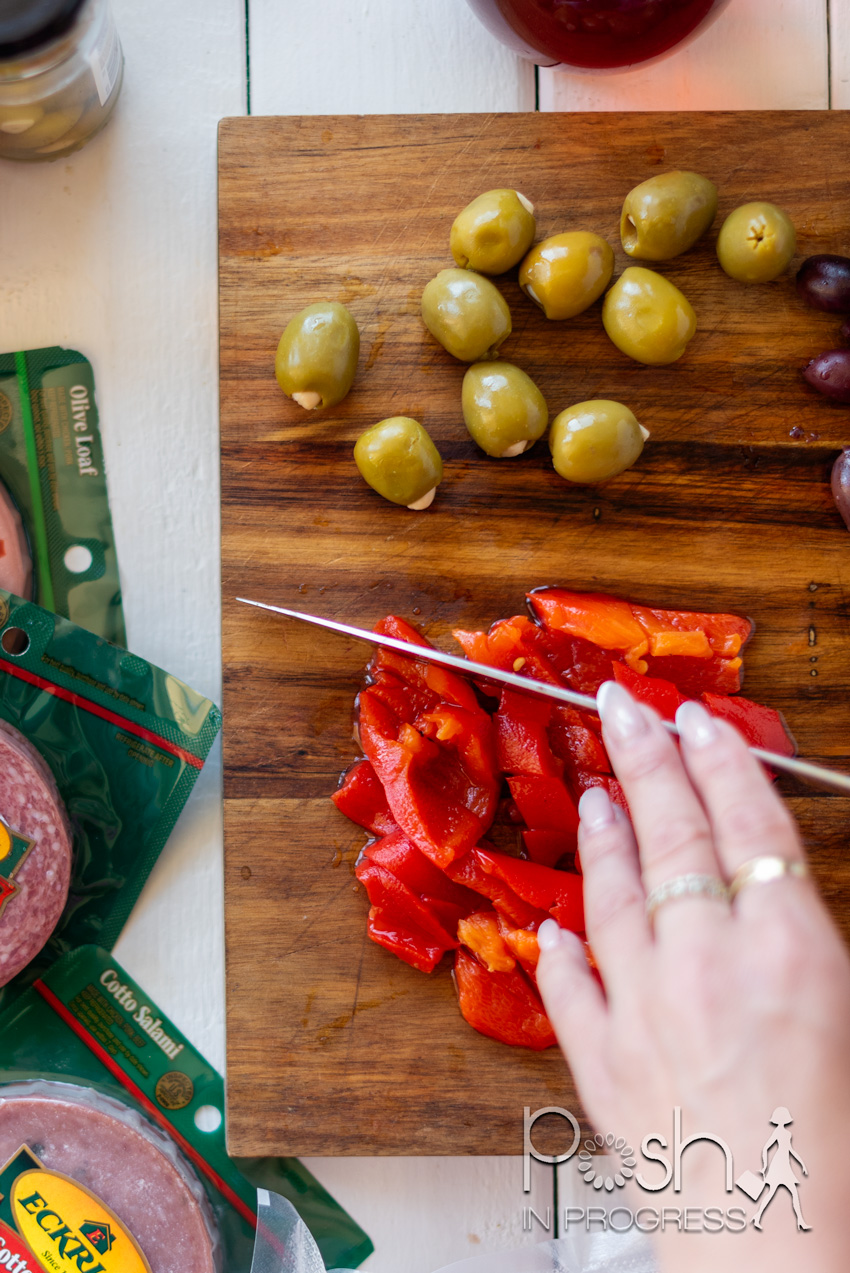muffuletta-recipe-02   Muffuletta Recipe by popular LA lifestyle blog, Posh in Progress: image of a woman cutting red peppers on a wooden cutting board next to some green olives.