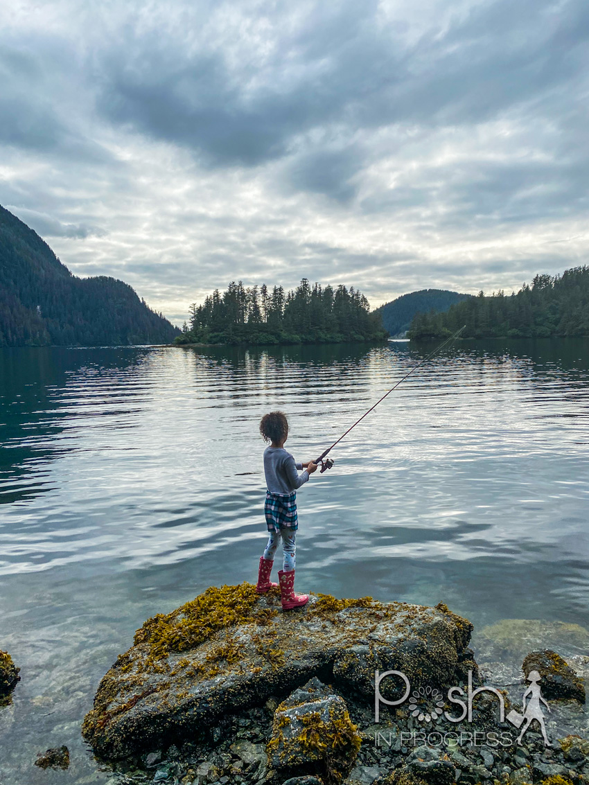 Things to do in Sitka Alaska by popular LA travel blog, Posh in Progress: image of a young girl standing on a rock and fishing.