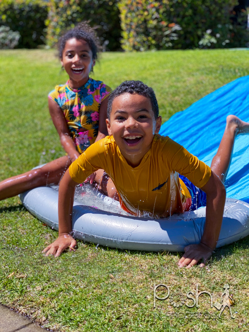 Backyard Water Toys by popular LA motherhood blog: image of a young boy and girl on a slip n slide.