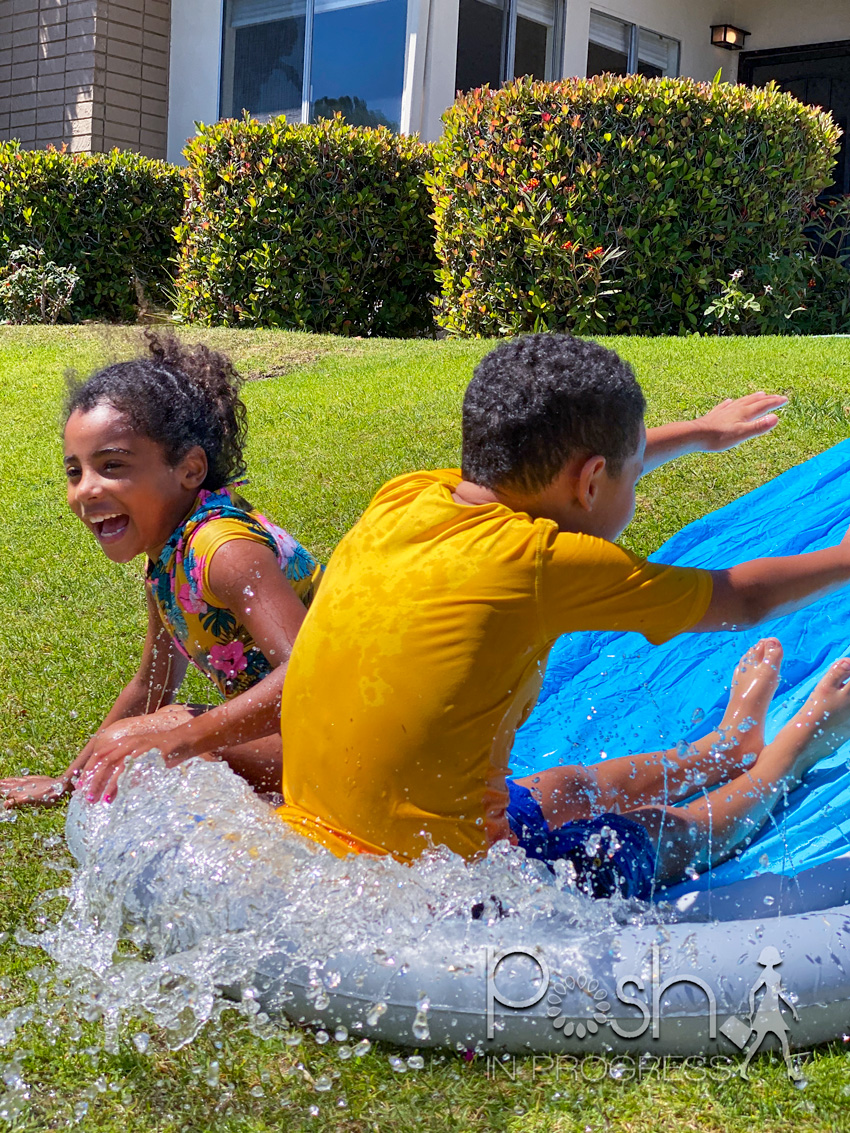 backyard water toys for kids | Backyard Water Toys by popular LA motherhood blog: image of a young boy and girl on a slip n slide.