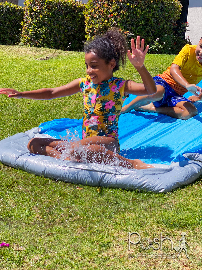 backyard water toys for kids 2 | Backyard Water Toys by popular LA motherhood blog: image of a young boy and girl on a slip n slide.