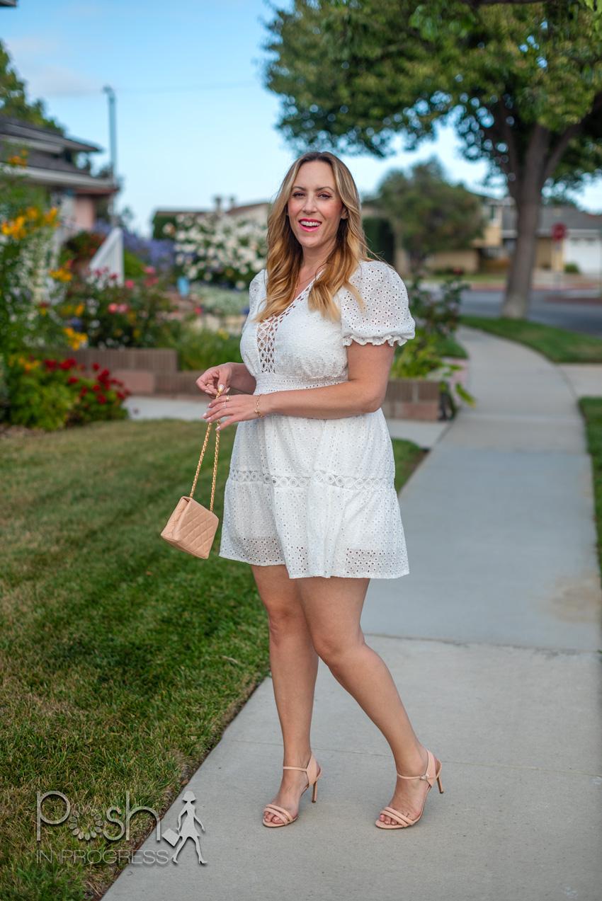 White Ruffle Hem Dress by popular LA fashion blog, Posh in Progress: image of a woman standing on a sidewalk and wearing a SheIn white ruffle hem dress. tan strap sandals and holding a tan handbag.